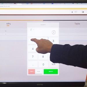 A supervisor enter actuals data into a touchscreen at the end of shift